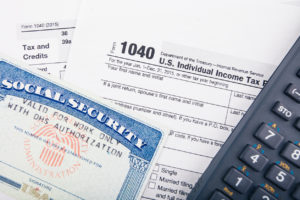 Tax return documents: Form 1040 - U.S. individual income tax return form and Social Security number card.